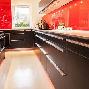 ハンブルクの中サイズのコンテンポラリースタイルのおしゃれなキッチン (一体型シンク、フラットパネル扉のキャビネット、黒いキャビネット、木材カウンター、赤いキッチンパネル、ガラス板のキッチンパネル、黒い調理設備、クッションフロア、白い床) の写真