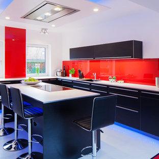 ハンブルクの中くらいのコンテンポラリースタイルのおしゃれなキッチン (一体型シンク、フラットパネル扉のキャビネット、黒いキャビネット、木材カウンター、赤いキッチンパネル、ガラス板のキッチンパネル、黒い調理設備、クッションフロア、白い床) の写真