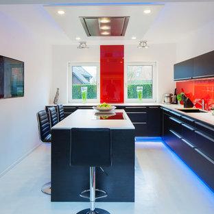 ハンブルクの中サイズのコンテンポラリースタイルのおしゃれなキッチン (フラットパネル扉のキャビネット、黒いキャビネット、木材カウンター、赤いキッチンパネル、ガラス板のキッチンパネル、一体型シンク、黒い調理設備、クッションフロア、白い床) の写真