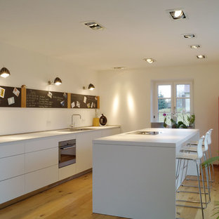 Mid-sized modern single-wall open plan kitchen in Nuremberg with flat-panel cabinets, white cabinets, solid surface benchtops, white splashback, slate splashback, with island and white benchtop.