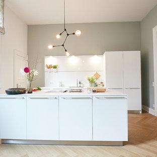Geschlossene, Zweizeilige, Mittelgroße Nordische Küche mit Einbauwaschbecken, flächenbündigen Schrankfronten, weißen Schränken, Küchenrückwand in Weiß, Elektrogeräten mit Frontblende, braunem Holzboden, Kücheninsel, braunem Boden, weißer Arbeitsplatte und Glasrückwand in Hamburg