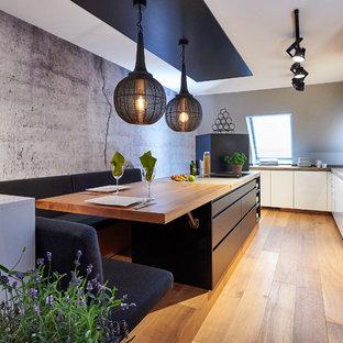 Geräumige Moderne Küche in L-Form mit flächenbündigen Schrankfronten, Betonarbeitsplatte, Kücheninsel, grauer Arbeitsplatte, weißen Schränken und hellem Holzboden in München