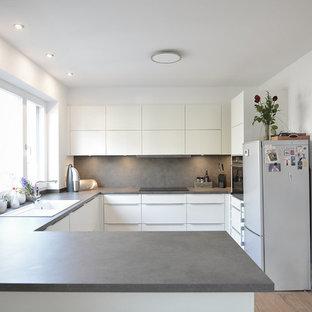 フランクフルトの巨大なモダンスタイルのおしゃれなキッチン (ドロップインシンク、フラットパネル扉のキャビネット、白いキャビネット、グレーのキッチンパネル、シルバーの調理設備、淡色無垢フローリング、アイランドなし、グレーのキッチンカウンター、木材カウンター、木材のキッチンパネル、茶色い床) の写真