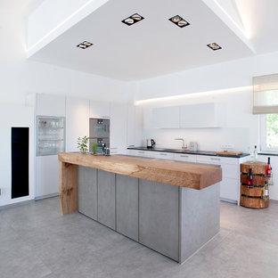 Moderne Küche mit Waschbecken, flächenbündigen Schrankfronten, weißen Schränken, Küchengeräten aus Edelstahl, Betonboden, Kücheninsel, grauem Boden und schwarzer Arbeitsplatte in München