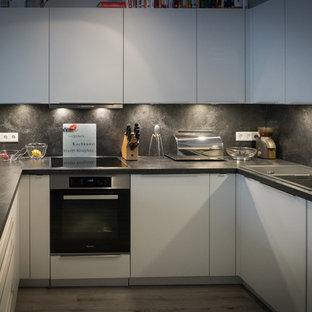 ニュルンベルクの巨大なコンテンポラリースタイルのおしゃれなキッチン (ドロップインシンク、フラットパネル扉のキャビネット、白いキャビネット、ラミネートカウンター、黒いキッチンパネル、木材のキッチンパネル、黒い調理設備、クッションフロア、黒いキッチンカウンター) の写真