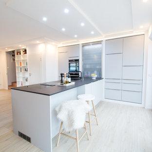 Große Moderne Wohnküche mit grauen Schränken, schwarzen Elektrogeräten, Halbinsel, beigem Boden, integriertem Waschbecken, flächenbündigen Schrankfronten und hellem Holzboden in Sonstige