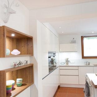 他の地域の中サイズのコンテンポラリースタイルのおしゃれなキッチン (ドロップインシンク、フラットパネル扉のキャビネット、白いキャビネット、白いキッチンパネル、ガラス板のキッチンパネル、シルバーの調理設備の、セラミックタイルの床、オレンジの床) の写真