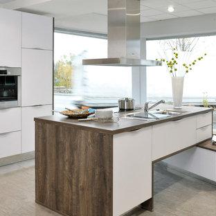 Zweizeilige, Mittelgroße Moderne Küche mit Einbauwaschbecken, flächenbündigen Schrankfronten, weißen Schränken, Arbeitsplatte aus Holz, Kücheninsel, beigem Boden, brauner Arbeitsplatte und Küchengeräten aus Edelstahl in Sonstige