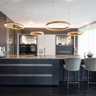 Große Moderne Küche mit Unterbauwaschbecken, flächenbündigen Schrankfronten, schwarzen Schränken, Elektrogeräten mit Frontblende, Halbinsel, schwarzem Boden und grauer Arbeitsplatte in Sonstige