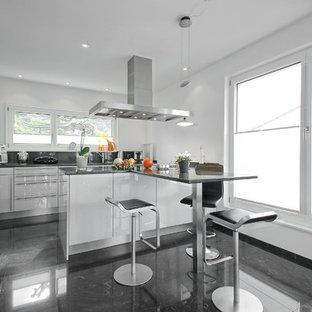 Moderne Küche in L-Form mit flächenbündigen Schrankfronten, weißen Schränken, Küchenrückwand in Grau, Küchengeräten aus Edelstahl, Halbinsel, schwarzem Boden und grauer Arbeitsplatte in Sonstige