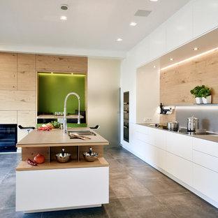 Immagine di una cucina contemporanea di medie dimensioni con lavello a doppia vasca, ante lisce, ante in legno chiaro, elettrodomestici neri, isola, pavimento grigio, paraspruzzi marrone, paraspruzzi in legno e pavimento in cementine