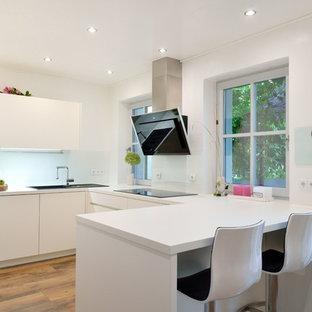 Offene, Kleine Moderne Küche in U-Form mit Einbauwaschbecken, flächenbündigen Schrankfronten, weißen Schränken, Küchenrückwand in Weiß, Glasrückwand, braunem Holzboden, Halbinsel, braunem Boden und weißer Arbeitsplatte in Nürnberg