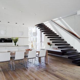 Einzeilige, Große Moderne Wohnküche mit flächenbündigen Schrankfronten, weißen Schränken, Küchengeräten aus Edelstahl, Kücheninsel, integriertem Waschbecken und dunklem Holzboden in Leipzig