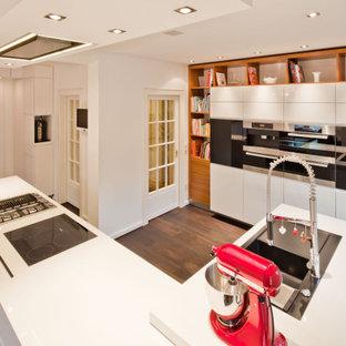 Moderne Küche in U-Form mit Einbauwaschbecken, flächenbündigen Schrankfronten, weißen Schränken, Küchengeräten aus Edelstahl, dunklem Holzboden, Kücheninsel, braunem Boden und weißer Arbeitsplatte in Hamburg