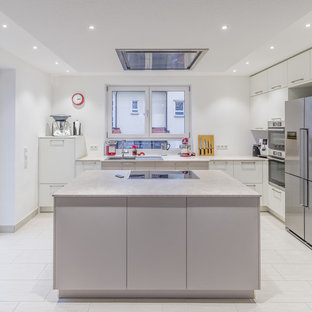 Photo of a mid-sized contemporary l-shaped open plan kitchen in Other with a drop-in sink, flat-panel cabinets, white cabinets, laminate benchtops, white splashback, stainless steel appliances, ceramic floors, with island, limestone splashback, beige floor and beige benchtop.