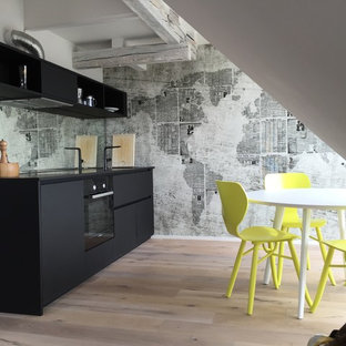 Mid-sized industrial single-wall eat-in kitchen in Cologne with flat-panel cabinets, black cabinets, mirror splashback, light hardwood floors, no island, black appliances, quartz benchtops, an integrated sink, multi-coloured splashback and brown floor.
