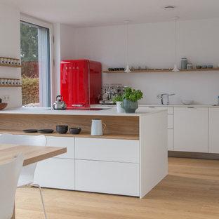 Zweizeilige Moderne Küche mit Unterbauwaschbecken, flächenbündigen Schrankfronten, weißen Schränken, bunten Elektrogeräten, braunem Holzboden, Halbinsel, braunem Boden und weißer Arbeitsplatte in München