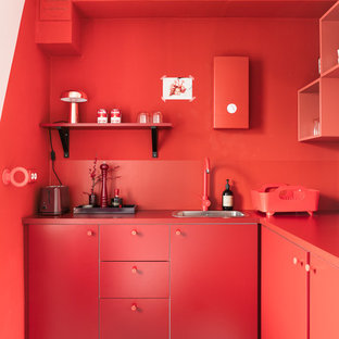 Small contemporary l-shaped kitchen in Berlin with flat-panel cabinets, red cabinets, red splashback, linoleum floors, no island, a single-bowl sink and red benchtop.