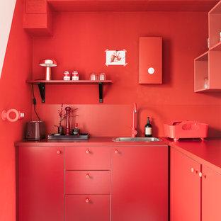 ベルリンの小さいコンテンポラリースタイルのおしゃれなL型キッチン (フラットパネル扉のキャビネット、赤いキャビネット、赤いキッチンパネル、リノリウムの床、アイランドなし、シングルシンク、赤いキッチンカウンター) の写真