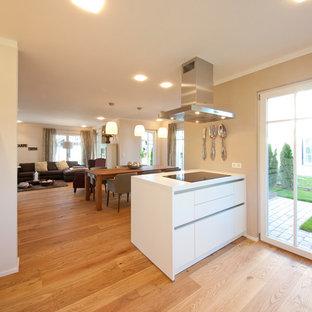 ミュンヘンの大きいコンテンポラリースタイルのおしゃれなキッチン (ドロップインシンク、フラットパネル扉のキャビネット、白いキャビネット、木材カウンター、茶色いキッチンパネル、木材のキッチンパネル、シルバーの調理設備、無垢フローリング、茶色い床、白いキッチンカウンター) の写真