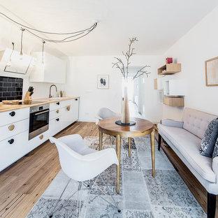 デュッセルドルフの中くらいの北欧スタイルのおしゃれなキッチン (フラットパネル扉のキャビネット、白いキャビネット、木材カウンター、黒いキッチンパネル、サブウェイタイルのキッチンパネル、シルバーの調理設備、無垢フローリング、アイランドなし、ドロップインシンク) の写真