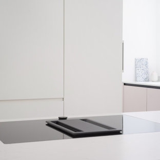 Large modern eat-in kitchen ideas - Example of a large minimalist galley linoleum floor and gray floor eat-in kitchen design in Berlin with a drop-in sink, flat-panel cabinets, pink cabinets, quartz countertops, white backsplash, window backsplash, paneled appliances, an island and white countertops
