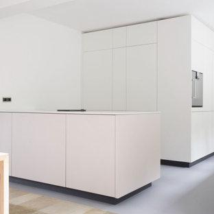 Idéer för att renovera ett stort funkis vit vitt kök, med en nedsänkt diskho, släta luckor, bänkskiva i kvarts, vitt stänkskydd, fönster som stänkskydd, integrerade vitvaror, linoleumgolv, en köksö och grått golv