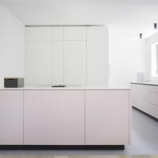 ベルリンの広いモダンスタイルのおしゃれなキッチン (ドロップインシンク、フラットパネル扉のキャビネット、ピンクのキャビネット、クオーツストーンカウンター、白いキッチンパネル、ガラスまたは窓のキッチンパネル、パネルと同色の調理設備、リノリウムの床、グレーの床、白いキッチンカウンター) の写真
