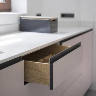 Пример оригинального дизайна: большая параллельная кухня в стиле модернизм с обеденным столом, накладной раковиной, плоскими фасадами, розовой кухней, столешницей из кварцевого агломерата, белым фартуком, фартуком с окном, техникой под мебельный фасад, полом из линолеума, островом, серым полом и белой столешницей