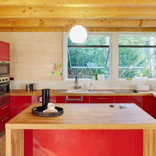 ベルリンの大きいコンテンポラリースタイルのおしゃれなキッチン (フラットパネル扉のキャビネット、赤いキャビネット、木材カウンター、ドロップインシンク、白いキッチンパネル、シルバーの調理設備の) の写真