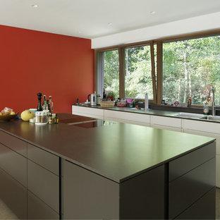 フランクフルトの広いコンテンポラリースタイルのおしゃれなキッチン (ドロップインシンク、フラットパネル扉のキャビネット、黒いキャビネット) の写真