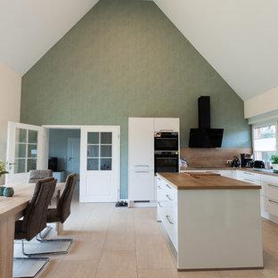 ブレーメンの大きいコンテンポラリースタイルのおしゃれなキッチン (白いキャビネット、木材カウンター、茶色いキッチンパネル、ドロップインシンク、フラットパネル扉のキャビネット、木材のキッチンパネル、黒い調理設備、無垢フローリング、茶色い床、茶色いキッチンカウンター) の写真