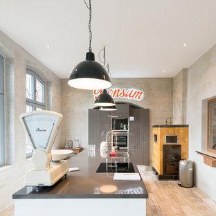 ベルリンの広いエクレクティックスタイルのおしゃれなアイランドキッチン (ドロップインシンク、フラットパネル扉のキャビネット、グレーのキャビネット) の写真
