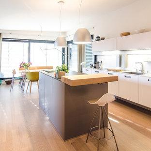 Zweizeilige, Mittelgroße Moderne Wohnküche mit Kücheninsel, flächenbündigen Schrankfronten, Küchenrückwand in Weiß, hellem Holzboden und beigem Boden in Frankfurt am Main