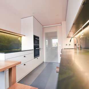 Inspiration for a mid-sized scandinavian galley separate kitchen in Munich with a single-bowl sink, flat-panel cabinets, white cabinets, granite benchtops, green splashback, stone slab splashback, black appliances, concrete floors, no island, grey floor and green benchtop.