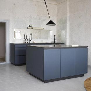 ベルリンの中くらいのモダンスタイルのおしゃれなキッチン (ドロップインシンク、フラットパネル扉のキャビネット、青いキャビネット、御影石カウンター、パネルと同色の調理設備、淡色無垢フローリング、白い床、黒いキッチンカウンター) の写真