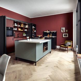 Offene, Große Asiatische Küche in L-Form mit flächenbündigen Schrankfronten, schwarzen Schränken, Küchenrückwand in Rot, schwarzen Elektrogeräten, Kücheninsel und weißer Arbeitsplatte in Nürnberg