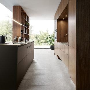 Zweizeilige, Mittelgroße Moderne Küche mit flächenbündigen Schrankfronten, Schieferboden, Kücheninsel, brauner Arbeitsplatte, dunklen Holzschränken, grauem Boden, Einbauwaschbecken und Elektrogeräten mit Frontblende in Nürnberg