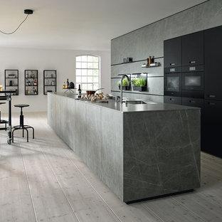 Offene, Zweizeilige Industrial Küche mit flächenbündigen Schrankfronten, grauen Schränken, schwarzen Elektrogeräten, grauer Arbeitsplatte, Kücheninsel und Küchenrückwand in Grau in Nürnberg