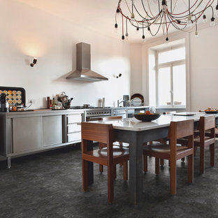 Photo of a mid-sized industrial single-wall eat-in kitchen in Cologne with an integrated sink, stainless steel appliances, vinyl floors, stainless steel cabinets, stainless steel benchtops, white splashback and no island.