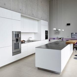 Moderne Küche mit Waschbecken, flächenbündigen Schrankfronten, weißen Schränken, Küchenrückwand in Weiß, Küchengeräten aus Edelstahl, Kücheninsel, beigem Boden und grauer Arbeitsplatte in Bremen