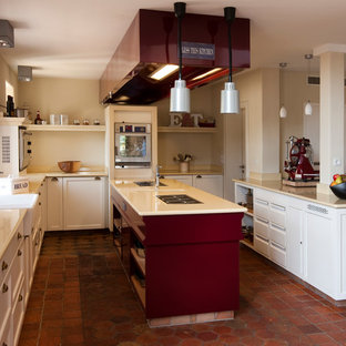 Inspiration for a mid-sized country u-shaped open plan kitchen in Berlin with a farmhouse sink, recessed-panel cabinets, white cabinets, beige splashback, stainless steel appliances, brick floors, multiple islands and red floor.
