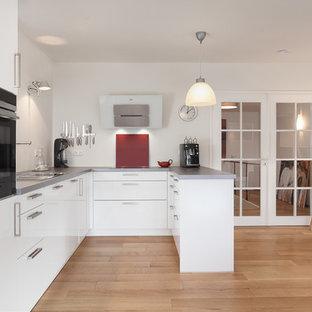 Scandinavian open concept kitchen inspiration - Example of a danish u-shaped light wood floor open concept kitchen design in Munich with a drop-in sink, white cabinets, red backsplash, black appliances and a peninsula