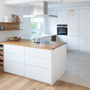 Idéer för att renovera ett litet funkis brun brunt kök, med en nedsänkt diskho, släta luckor, vita skåp, träbänkskiva, vitt stänkskydd, svarta vitvaror, kalkstensgolv, beiget golv och en halv köksö