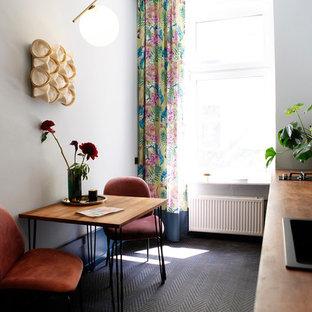 ベルリンの小さいエクレクティックスタイルのおしゃれなI型キッチン (フラットパネル扉のキャビネット、黒いキャビネット、木材カウンター、セラミックタイルのキッチンパネル、アイランドなし、黒い床) の写真