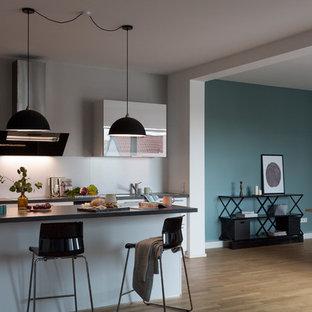 ベルリンの巨大なコンテンポラリースタイルのおしゃれなキッチン (無垢フローリング、茶色い床、ドロップインシンク、フラットパネル扉のキャビネット、白いキャビネット、白いキッチンパネル、シルバーの調理設備の、黒いキッチンカウンター、大理石カウンター、セメントタイルのキッチンパネル) の写真