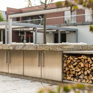 ライプツィヒの広いインダストリアルスタイルのおしゃれなI型キッチン (ステンレスキャビネット、ライムストーンカウンター) の写真
