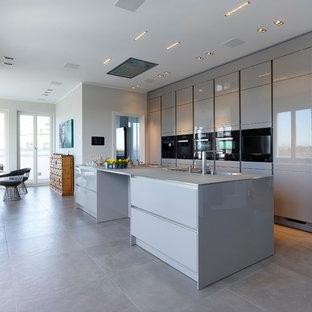 Offene, Zweizeilige, Große Moderne Küche mit integriertem Waschbecken, flächenbündigen Schrankfronten, grauen Schränken, schwarzen Elektrogeräten, Zementfliesen, Kücheninsel und grauem Boden in Düsseldorf