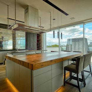 Geräumige Moderne Wohnküche mit flächenbündigen Schrankfronten, grauen Schränken, Arbeitsplatte aus Holz, Rückwand aus Glasfliesen, braunem Holzboden, Kücheninsel und integriertem Waschbecken in Hamburg