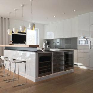 Offene, Mittelgroße Moderne Küche in L-Form mit flächenbündigen Schrankfronten, weißen Schränken, Arbeitsplatte aus Holz, Küchenrückwand in Grau, weißen Elektrogeräten, Kücheninsel, braunem Boden und braunem Holzboden in München